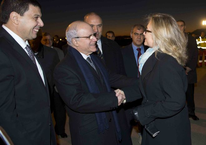 Algerian Foreign Minister Mourad Medelci, centre, greets U.S. Secretary of State Hillary Rodham Clinton upon her arrival at Houari Boumediene Airport, in Algiers, Algeria, Monday, Oct. 29, 2012. Clinton is on a five-day trip overseas to increase pressure on Mali's al-Qaeda-linked rebels and help Balkan nations end long-simmering ethnic and political disagreements. (AP Photo, Saul Loeb, Pool)