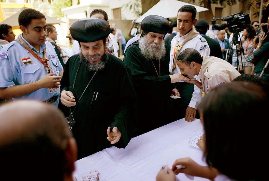 Two Coptic clergymen, center, register for voting with election workers during the new Coptic Pope elections at the main Coptic cathedral in Cairo, Egypt, Monday, Oct. 29, 2012. A council of Egypt's Coptic Christians is voting Monday in a process that will elect a new spiritual leader for the ancient church as the community struggles to assert its identity and role amid a rising tide of Islamism that has left many Copts fearful for their future. (AP Photo/Nasser Nasser)