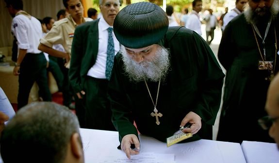** FILE ** A Coptic clergyman registers for voting with election workers during the new Coptic Pope elections at the main Coptic cathedral in Cairo, Egypt, Monday, Oct. 29, 2012. (AP Photo/Nasser Nasser)