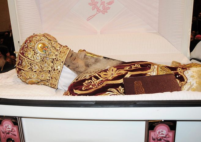 FILE - The body of Pope Shenouda III lies in a casket at the Coptic Orthodox cathedral during his funeral in Cairo, Egypt, in this Tuesday, March 20, 2012 file photo. A council of Egypt's Coptic Christians is voting Monday Oct 29 2012 on a new spiritual leader to the ancient church as the community grapples with the rising powers of Islamists. The charismatic Pope Shenouda III died in March, at the age of 88 and after 40 years as the leader of the Coptic Orthodox Church. The congregation represents the majority of Egypt's Christians, who make up about 10 per cent of the country's 83 million people. About 2,400 clergymen, community leaders, and Coptic church notables are voting Monday to short-list three candidates from among three monks and two bishops. The final selection is due Sunday. (AP Photo/Mohammed Asad, file)