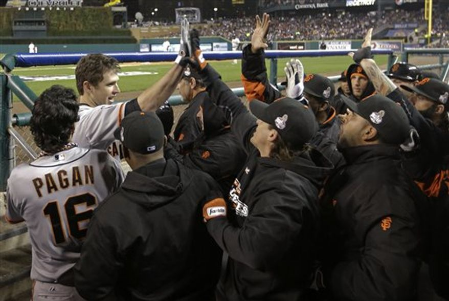 San Francisco Giants catcher Buster Posey celebrates in the dugout after hitting two-run home run during the sixth inning of Game 4 of baseball's World Series against the Detroit Tigers Sunday, Oct. 28, 2012, in Detroit. (AP Photo/David J. Phillip)