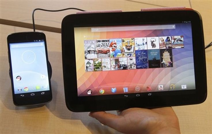 The Nexus 4 smartphone, left and the Nexus 10 tablet are shown by Randall Safara of Google at a Google announcement in San Francisco, Monday, Oct. 29, 2012. Google is adding a few more gadgets to holiday shopping lists. The devices announced Monday include the latest in Google's line of Nexus smartphones and a larger version of the 7-inch tablet that the company began selling in July under the Nexus brand. (AP Photo/Jeff Chiu)