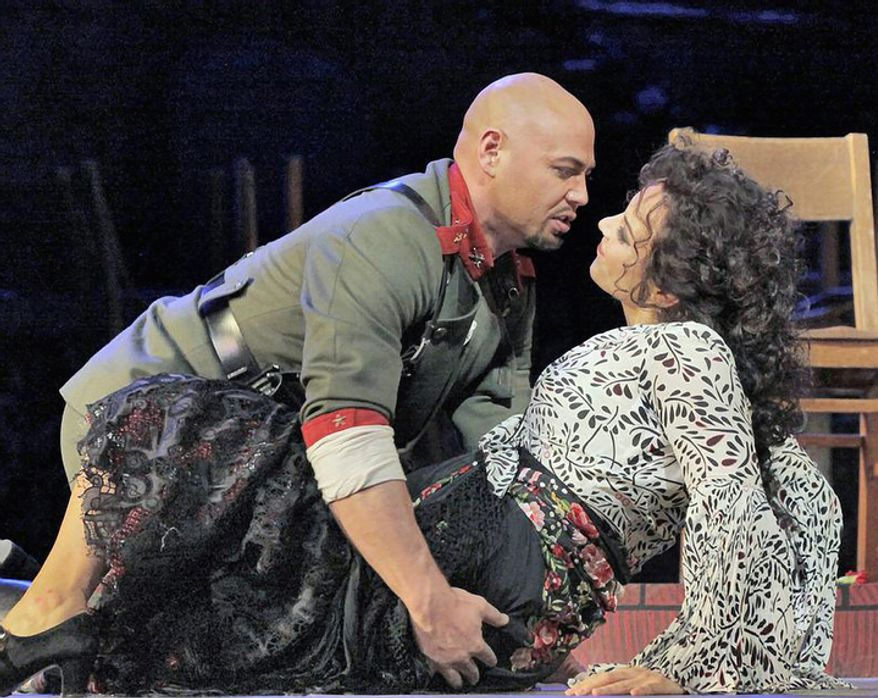 """Keith Miller, left, plays Zuniga in Bizet's """"Carmen"""" with Elina Garanca in the title role at the Metropolitan Opera in New York. Miller, a former University of Colorado fullback, has reinvented himself, going from the gridiron to the stage and will appear in Verdi's """"Un Ballo in Maschera,"""" at the Metropolitan Opera. Performances begin Thursday, Nov. 8, 2012. (AP Photo/Metropolitan Opera, Ken Howard)"""