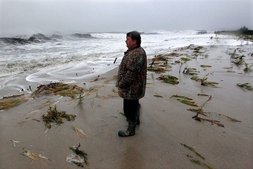 Lifelong Cape May resident Andy Becica watches rough surf pound the beach on Monday morning, Oct. 29, 2012, in Cape May, N.J., as high tide and Hurricane Sandy begin to arrive. Mr. Becica said this was the worst he's seen the ocean. Hurricane Sandy continued on its path Monday, forcing the shutdown of mass transit, schools and financial markets; sending coastal residents fleeing; and threatening a dangerous mix of high winds and soaking rain.  (AP Photo/Mel Evans)