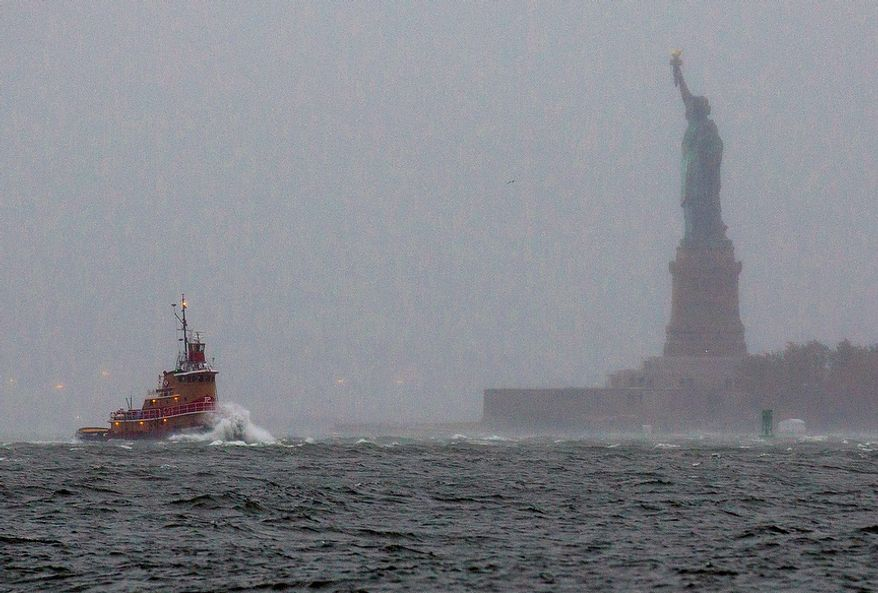 Waves crash over the bow of a tugboat as it passes near the Statue of Liberty in New York on Monday, Oct. 29, 2012, as rough water as the result of Hurricane Sandy churned the waters of New York Harbor. Hurricane Sandy continued on its path Monday, forcing the shutdown of mass transit, schools and financial markets; sending coastal residents fleeing; and threatening a dangerous mix of high winds and soaking rain. (AP Photo/Craig Ruttle)