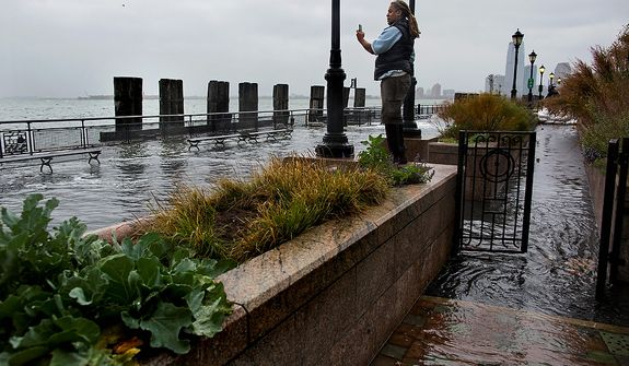 Alix Brignol of New York takes a picture as water washes over the seawall near high tide at Battery Park in New York on Monday, Oct. 29, 2012, as Hurricane Sandy approaches the East Coast.Hurricane Sandy continued on its path Monday, forcing the shutdown of mass transit, schools and financial markets; sending coastal residents fleeing; and threatening a dangerous mix of high winds and soaking rain. (AP Photo/Craig Ruttle)