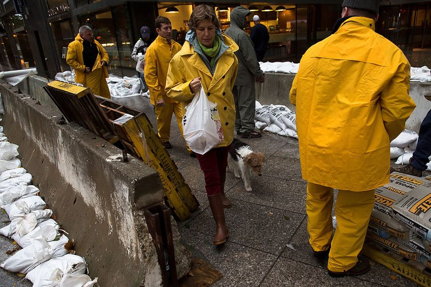 A pedestrian walks her dog through a working crew as they stack sandbags beside concrete barriers to protect buildings near the World Financial Center in anticipation of massive flooding on Monday, Oct. 29, 2012, in New York. Hurricane Sandy bore down on the Eastern Seaboard's largest cities Monday, forcing the shutdown of mass transit, schools and financial markets; sending coastal residents fleeing; and threatening a dangerous mix of high winds, soaking rain and a seawater surge of anywhere from 6 to 11 feet. (AP Photo/John Minchillo)