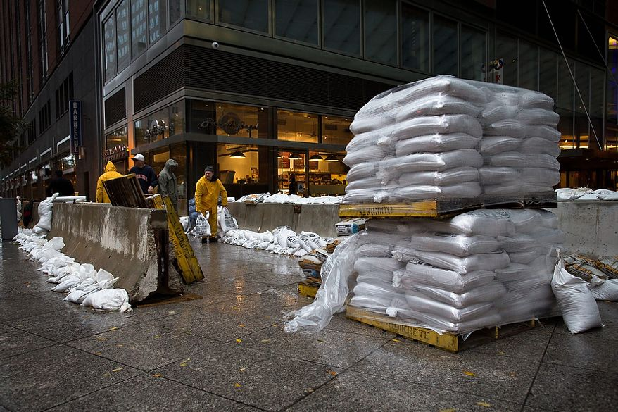 Workers stack sandbags beside concrete barriers to protect buildings near the World Financial Center in anticipation of flooding on Monday, Oct. 29, 2012, in New York. Hurricane Sandy bore down on the Eastern Seaboard's largest cities Monday, forcing the shutdown of mass transit, schools and financial markets; sending coastal residents fleeing; and threatening a dangerous mix of high winds, soaking rain and a seawater surge of anywhere from 6 to 11 feet. (AP Photo/ John Minchillo)