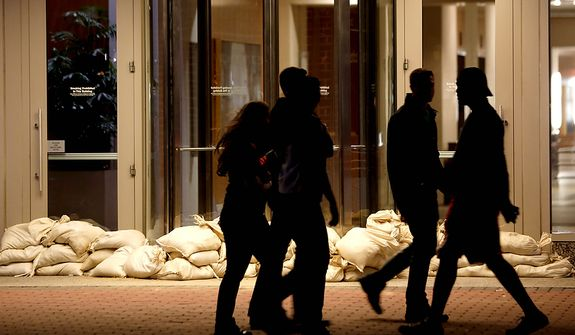 Sandbags line the entrance of a building as people walk by near the Hudson River waterfront on Sunday, Oct. 28, 2012, in Hoboken, N.J. Tens of thousands of people were ordered to evacuate coastal areas Sunday as big cities and small towns across the Northeast braced for the onslaught of a superstorm threatening some 60 million people along the most heavily populated corridor in the nation. (AP Photo/Julio Cortez)