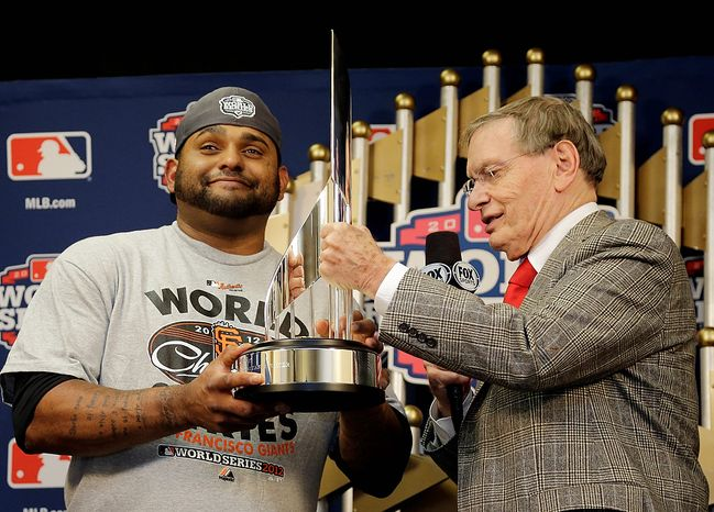Commissioner Bud Selig hands San Francisco Giants' Pablo Sandoval his MVP trophy after Game 4 of baseball's World Series against the Detroit Tigers Sunday, Oct. 28, 2012, in Detroit. The Giants won 4-3 to win the series. (AP Photo/Matt Slocum, Pool )