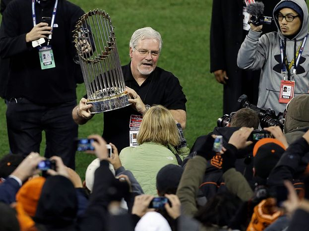 San Francisco Giants general manager Brian Sabean hold up the trophy after the Giants defeated the Detroit Tigers, 4-3, in Game 4 of baseball's World Series  Sunday, Oct. 28, 2012, in Detroit. The Giants won the World  Series 4-0.  (AP Photo/Paul Sancya )