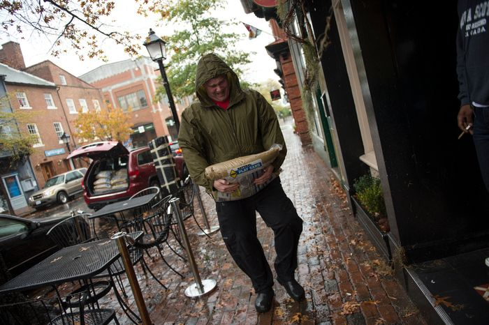 O'Connell's Restaurant General Manager Doug Gruenberg carries sand bags to put into place at the restaurant's doorsteps in Old Town Alexandria, Va., Monday, Oct. 29, 2012, while Hurricane Sandy makes it's way north along the Atlan