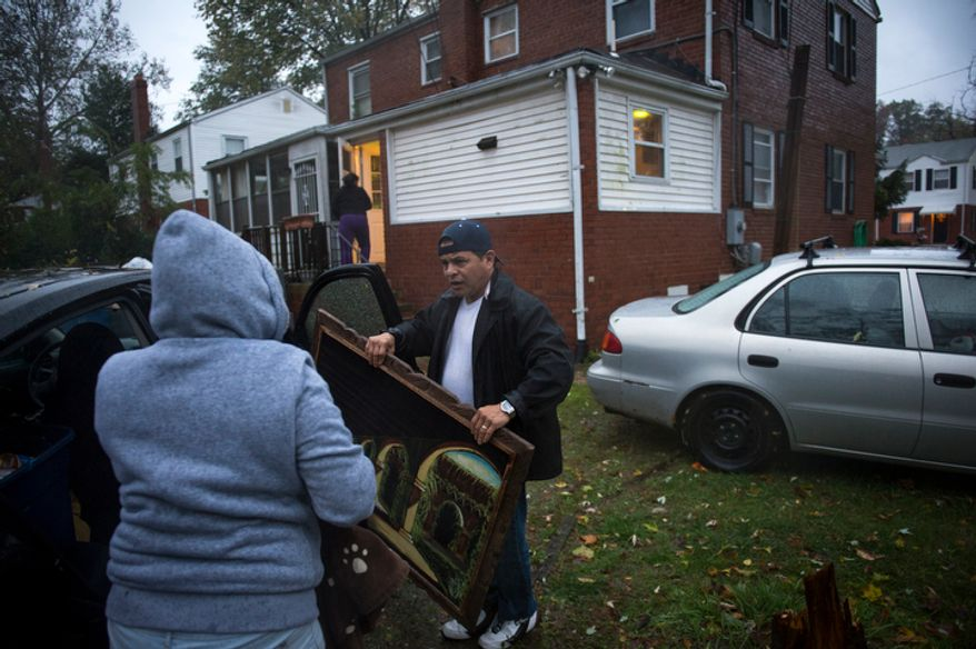 Members of the Merino family carry belongings to waiting cars as they leave their home on Arlington Terrace in the Huntington neighborhood of Alexandria, Va., on Oct. 29, 2012, during a mandatory evacuation order as high winds and heavy rain from Hurricane Sandy pound the Atlantic coast. (Rod Lamkey Jr./The Washington Times)