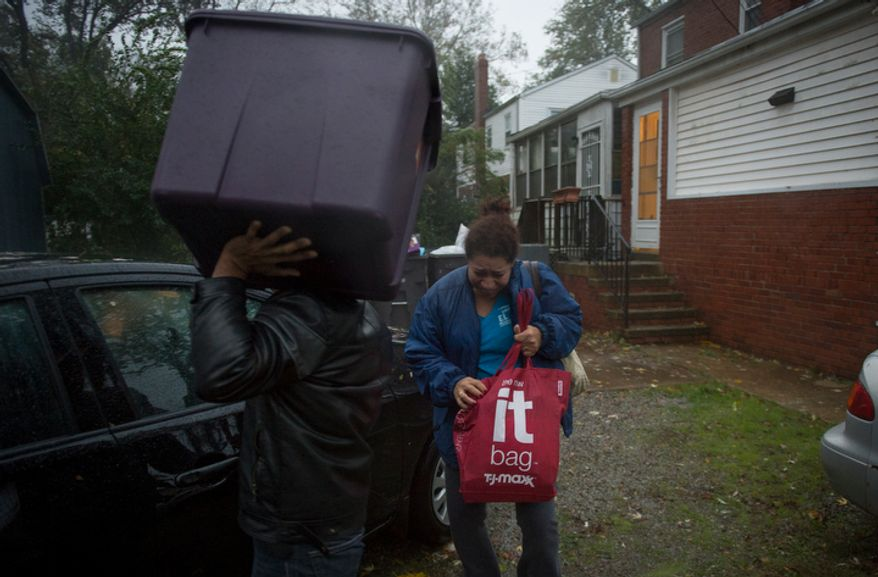 Rosa Merino and her family leave from their home on Arlington Terrace in the Huntington neighborhood of Alexandria, Va., on Oct. 29, 2012, during a mandatory evacuation order as high winds and heavy rain from Hurricane Sandy pound the Atlantic coast. (Rod Lamkey Jr./The Washington Times)