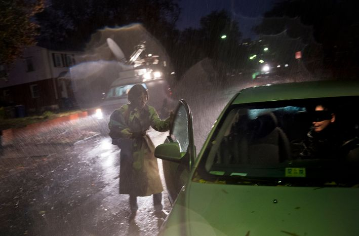 A woman leaves a house on Arlington Terrace in the Huntington neighborhood of Alexandria, Va., on Oct. 29, 2012, during a mandatory evacuation order as high winds and heavy rain from Hurricane Sandy pound the Atlantic coast. (Rod Lamkey Jr./The Washington Times)