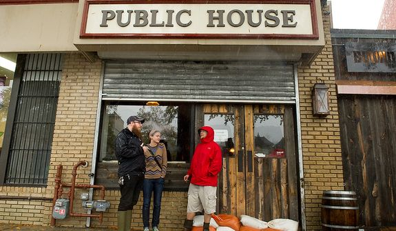 Left to right: Chris Keller, Katie Hooks, and Christopher Graham brave the wind and rain to have a cigarette outside of Boundary Stone, a bar along Rhode Island Avenue in the Bloomingdale neighborhood of Northwest, Washington, D.C., Monday, October 29, 2012. Hurricane Sandy begins to affect the Washington, D.C. region. (Andrew Harnik/The Washington Times)