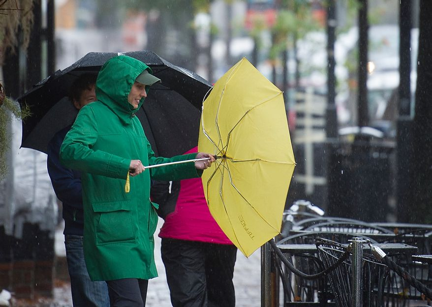 A woman tries to gain control of her umbrella in the wind in Old Town Alexandria, Va., Monday, Oct. 29, 2012, while Hurricane Sandy makes it's way north along the Atlantic coast. (Rod Lamkey Jr./The Washington Times)