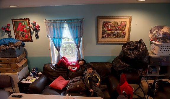 Leo, left, 3, and Jason Lemus, 8, sit on their sofa in their Huntington, Va. home on Monday, Oct. 29, 2012 surrounded by all the belongings from the basement, which their parents brought upstairs because they are sure their basement is going to flood due to Hurricane Sandy. Their basement flooded in September, and they said they had about 6 feet of water then. They are planning to go to a relative's house in Clinton, Md. if the house floods again. (Barbara L. Salisbury/The Washington Times)