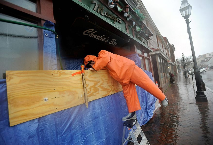 Charlie Priola, owner of Mangia's restaurant in Annapolis, Md., tries to protect his restaurant from Hurricane Sandy, Monday, Oct. 29, 2012. Hurricane Sandy continued on its path Monday, as the storm forced the shutdown of mass transit, schools and financial markets, sending coastal residents fleeing, and threatening a dangerous mix of high winds and soaking rain. (AP Photo/Steve Ruark)