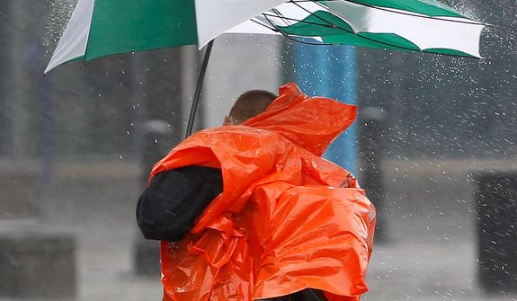 Pedestrian who try to cover from the rain try to control his umbrella from the heavy wins in Baltimore downtown as Hurricane Sandy approach in the coast of Maryland, on Monday,  Oct. 29,  2012. Hurricane Sandy continued on its path Monday, as the storm forced the shutdown of mass transit, schools and financial markets, sending coastal residents fleeing, and threatening a dangerous mix of high winds and soaking rain. (AP Photo/Jose Luis Magana)