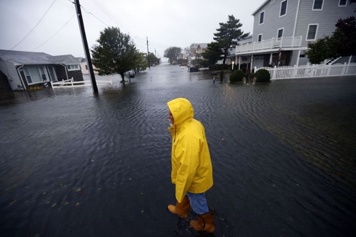Al Daisey walks in the floodwaters in front of his home in Fenwick Island, Del., on Monday, Oct. 29, 2012, as Hurricane Sandy bears down on the East Coast. (AP Photo/Alex Brandon)