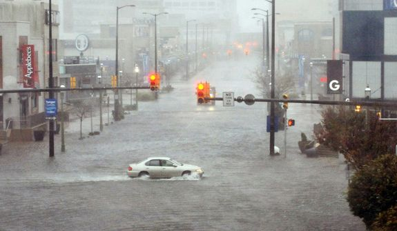 Flooding and high winds arrive along North Michigan Avenue in Atlantic City, N.J., Monday Oct. 29, 2012. Hurricane Sandy continued on its path Monday, as the storm forced the shutdown of mass transit, schools and financial markets, sending coastal residents fleeing, and threatening a dangerous mix of high winds and soaking rain. (AP Photo/The Press of Atlantic City, Michael Ein)