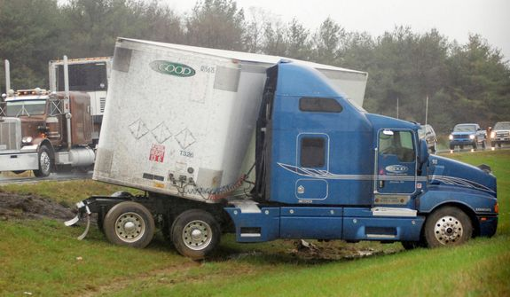 An 18-wheel tractor trailer belonging to the Extra Good Transport Services, Inc. based in Columbia, Pa., sits on a median strip after jacknifing along I-81 about 1/4 mile north of the West Virginia/Virginia border near Ridgeway, W.Va. on Monday, Oct 29, 2012. (AP Photo/The Journal, Ron Agnir)