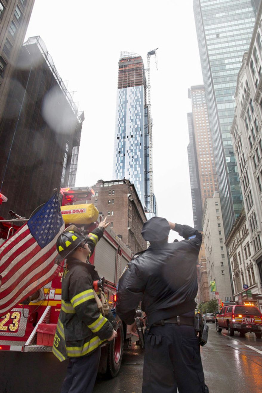 A FDNY firefighter and a New York police officer look up at a construction crane atop a luxury high-rise dangling precariously over the streets after collapsing in high winds from Hurricane Sandy, Monday, Oct. 29, 2012, in New York.  (AP Photo/John Minchillo)