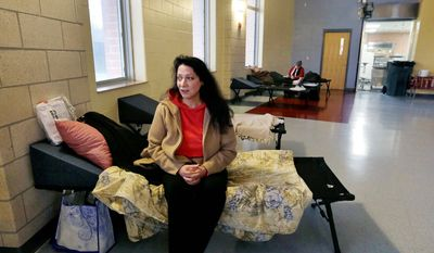 Diana Clarke sits on a cot set up by the Red Cross as she takes shelter from Hurricane Sandy at Weymouth High School in Weymouth, Mass. Monday, Oct. 29, 2012. (AP Photo/Elise Amendola)