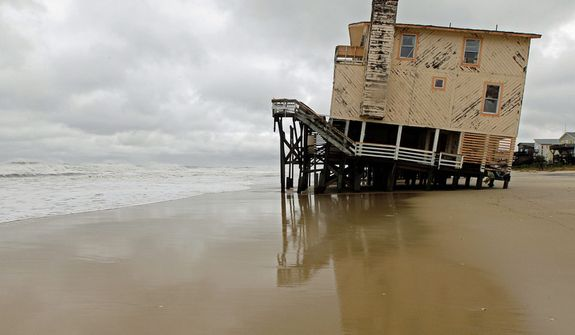 An abandoned beach house that survived the storm surge from Hurricane Sandy sits off center in Nags Head, N.C., Monday, Oct. 29, 2012. The storm continued on its path Monday, forcing  the shutdown of mass transit, schools and financial markets,  and sending coastal residents fleeing. (AP Photo/Gerry Broome)