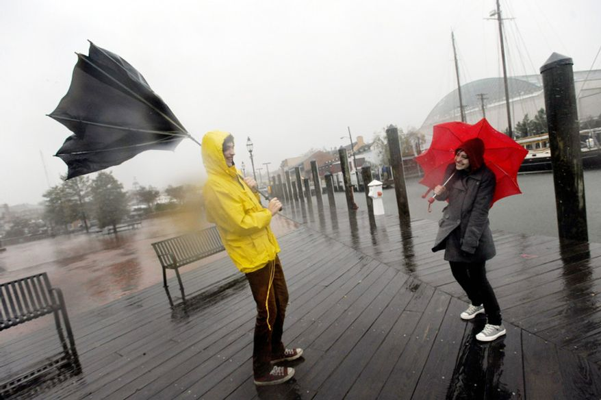 Jake Wilkerson, 20, and Kaityln Baker, 21, both of Annapolis, Md., struggle with their umbrellas as Hurricane Sandy approaches Annapolis Monday, Oct. 29, 2012. (AP Photo/Steve Ruark)