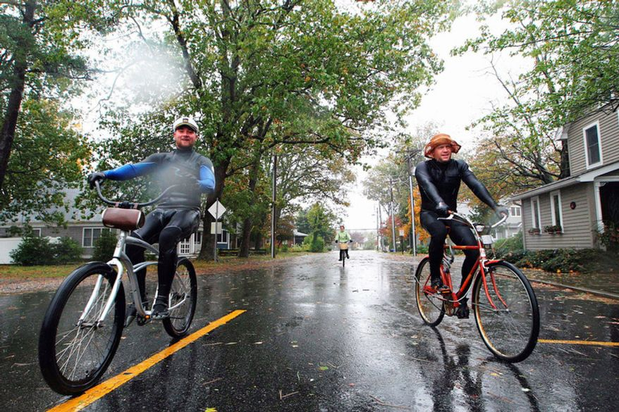 Rehoboth Beach residents ride their bikes around the neighborhood in wet suits in Delaware, Monday, Oct. 29, 2012.  (AP Photo/The Wilmington News-Journal, Suchat Pederson)
