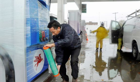 U.S. Fuel gas station store manager Tsewang Guyrme, of Phillipsburg, N.J., wraps one of his newly installed Mobil gas tanks with bubble and shrink wrap, Monday, Oct. 29, 2012, to protect them from possible flying debris in Phillipsburg. His station on Memorial Parkway is converting to a Mobil gas station. Hurricane Sandy continued on its path Monday, forcing the shutdown of mass transit, schools and financial markets, sending coastal residents fleeing for higher ground, and threatening a dangerous mix of high winds and soaking rain. (AP Photo/The Express-Times, Lisa Massey)