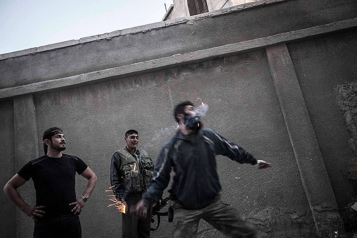 A rebel fighter throws a homemade grenade toward Syrian army troops on the front line in the Bustan Al-Pasha neighborhood of Aleppo, Syria, on Sunday, Oct. 28, 2012. Syria's air force fired missiles and dropped barrel bombs on rebel strongholds while opposition fighters attacked regime positions, flouting a U.N.-backed cease-fire that was supposed to quiet fighting over a long holiday weekend but never took hold. (AP Photo/Narciso Contreras)