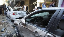 In this photo released by the Syrian official news agency SANA, Syrian citizens gather next to cars that were destroyed by a car bomb, at Jaramana neighborhood, in Damascus, Syria, Monday Oct. 29, 2012. A Syrian government official says a car bomb in a Damascus suburb has killed 10 people. The official said the blast on Monday in Jaramana also wounded 41 people and caused heavy damage. He spoke on condition of anonymity because he was not authorized to speak to the media. (AP Photo/SANA)