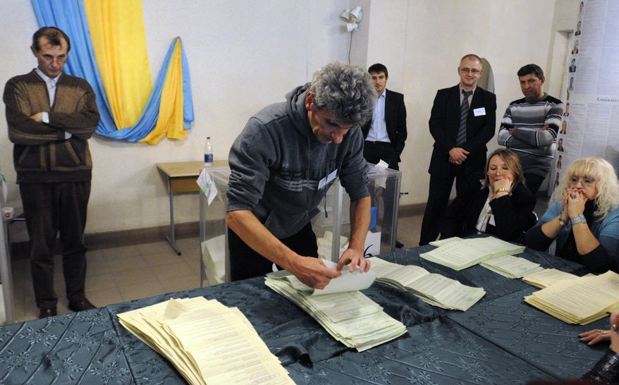 Election commission officials count ballots in Ukraine's parliamentary elections at a polling station in Kiev on Sunday, Oct. 28, 2012. (AP Photo/Sergei Chuzavkov)