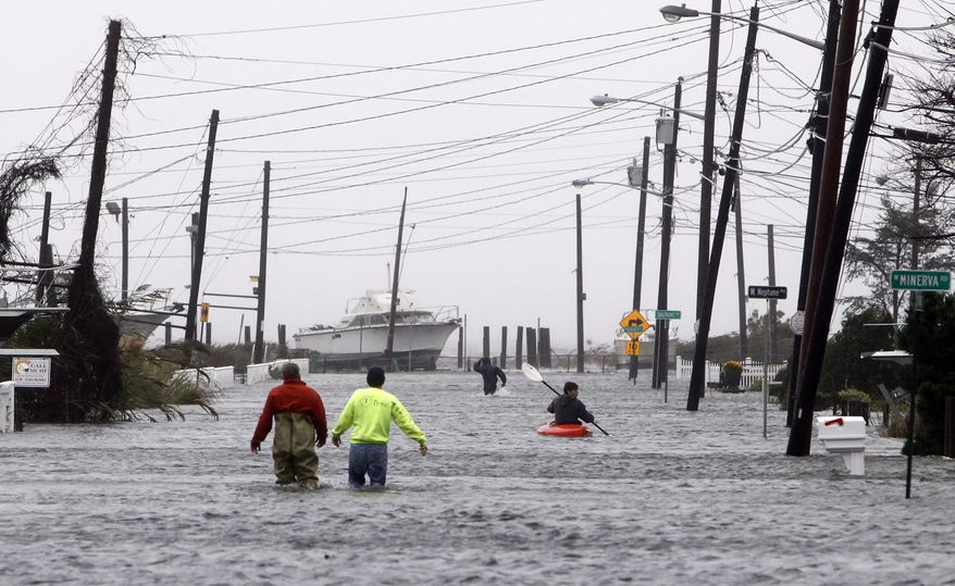 People wade and paddle down a flooded street as Hurricane Sandy approaches, Monday, Oct. 29, 2012, in Lindenhurst, N.Y. (AP Photo/Jason DeCrow)