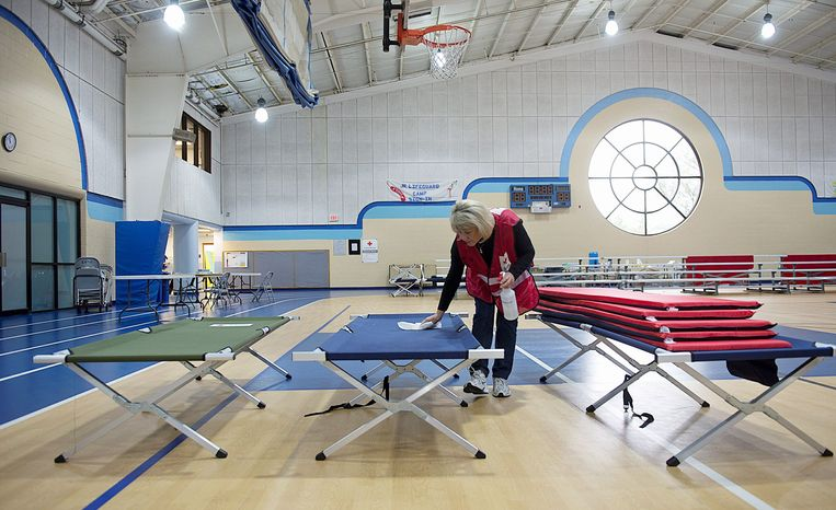 Red Cross volunteer Julie Tarascio wipes a cot in the Lee District RECenter south of Alexandria on Tuesday. The center became an animal-friendly shelter for people evacuated from their homes because of Hurricane Sandy. About two dozen people stayed there Monday night, the youngest 7 weeksold. (Barbara L. Salisbury/The Washington Times)