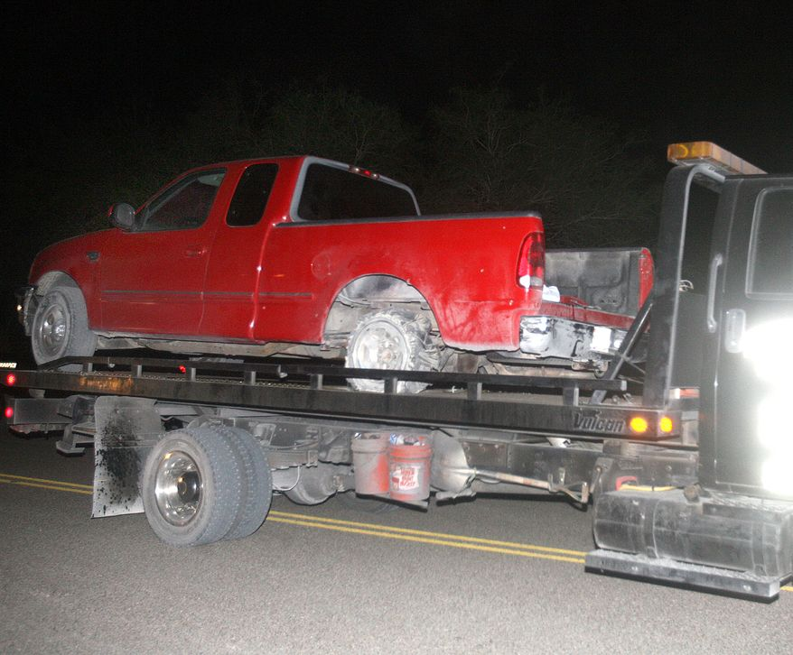 ** FILE ** A red pickup truck is moved from the scene of a incident after a chase between law enforcement and suspected human smugglers north of La Joya, Texas, on Thursday, Oct. 25, 2012. A Texas Department of Public Safety sharpshooter opened fire on an evading vehicle loaded with suspected illegal immigrants, leaving at least two people dead, sources familiar with the investigation said. (AP Photo/The Monitor, Joel Martinez)