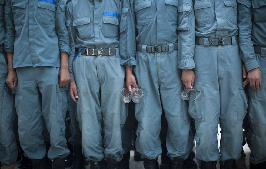 Afghan National Police officers line up with their tea glasses before breakfast at the Police Academy in Kabul, Afghanistan, on Tuesday, Oct. 9, 2012. (AP Photo/Anja Niedringhaus)