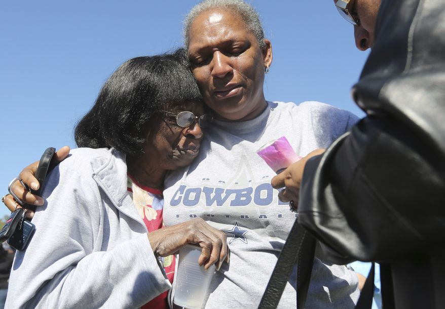 Verna Oates (right) and Flora Ford comfort each other outside the Greater Sweethome Missionary Baptist Church in Forest Hill, Texas, where an attacker killed the church's pastor on Monday, Oct. 29, 2012 (AP Photo/LM Otero)
