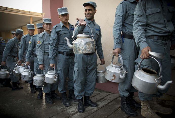 Afghan National Police officers line up with pots to get their breakfast at the Police Academy in Kabul, Afghanistan, Tuesday, Oct. 9, 2012. NATO defense leaders gathering in Brussels Tuesday are committed to the war in Afghanistan, according to U.S. and alliance officials, but there ar