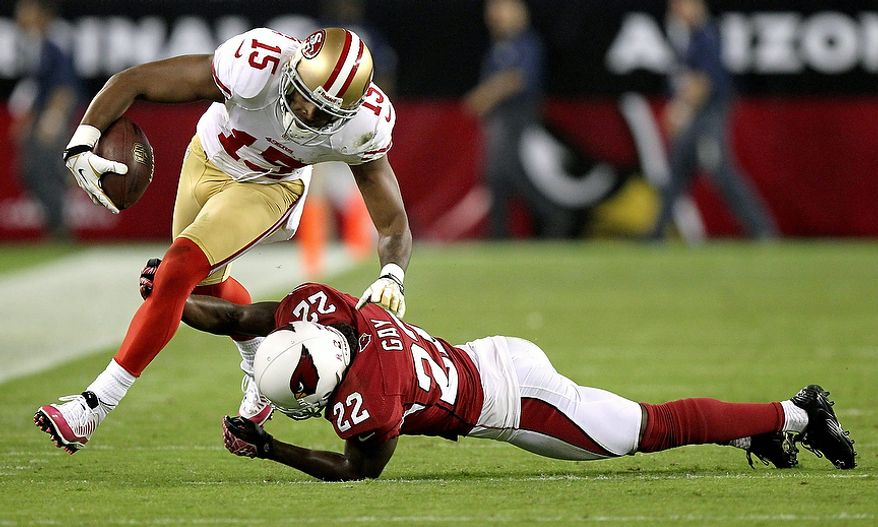 San Francisco 49ers wide receiver Michael Crabtree (15) breaks the tackle of Arizona Cardinals cornerback William Gay (22) during the first half of an NFL football game on Monday, Oct. 29, 2012, in Glendale, Ariz. (AP Photo/Paul Connors)