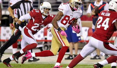 San Francisco 49ers wide receiver Randy Moss (84) runs in a touchdown after a reception as Arizona Cardinals cornerback Jamell Fleming (23) pursues during the second half of an NFL football game on Monday, Oct. 29, 2012, in Glendale, Ariz. (AP Photo/Paul Connors)