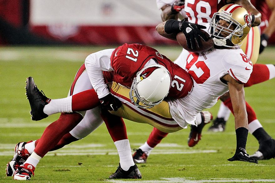Arizona Cardinals cornerback Patrick Peterson (21) tackles San Francisco 49ers wide receiver Mario Manningham (82) during the first half of an NFL football game, Monday, Oct. 29, 2012, in Glendale, Ariz. (AP Photo/Matt York)