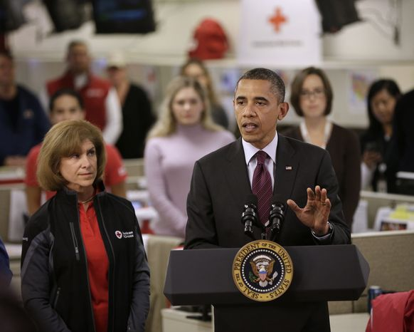 President Barack Obama, accompanied by American Red Cross President and CEO Gail J. McGovern, gestures while speaking during the his visit to the Disaster Operation Center of the Red Cross National He