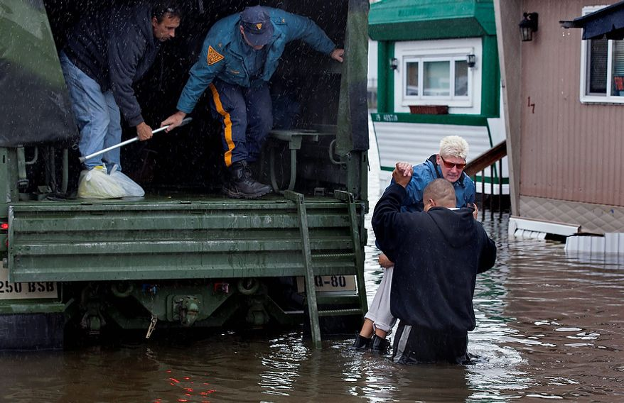A woman is lifted into a National Guard vehicle after leaving her flooded home at the Metropolitan Trailer Park in Moonachie, N.J. Tuesday, Oct. 30, 2012, after supsterstorm Sandy. Sandy, which was downgraded from hurricane just before making landfall, caused multiple fatalities, halted mass transit and cut power to more than 6 million homes and businesses. (AP Photo/Craig Ruttle)