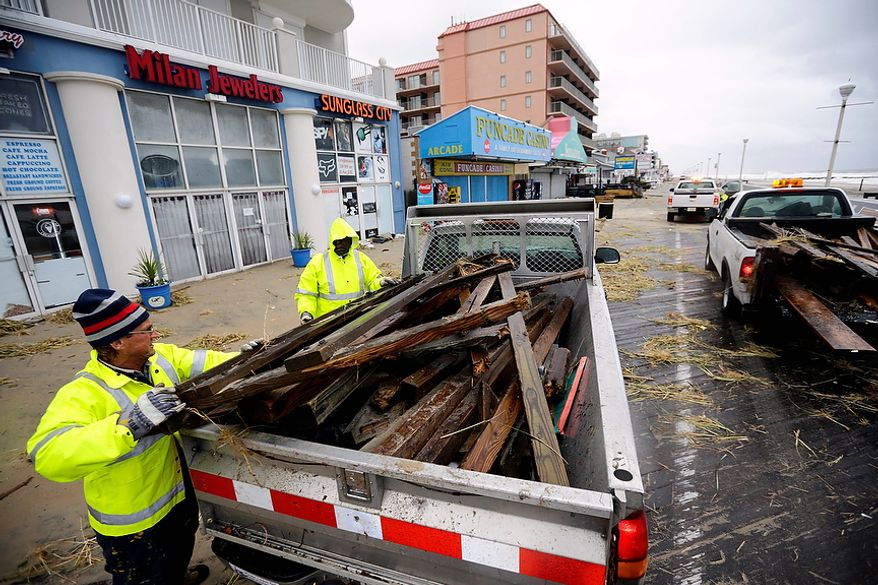 Michael Brown, left, and Enos Jones, with Ocean City, fill a truck with debris as they clean the boardwalk after the effects of Hurricane Sandy Tuesday, Oct. 30, 2012, in Ocean City, Md. Sandy, the storm that made landfall Monday, caused multiple fatalities, halted mass transit and cut power to more than 6 million homes and businesses.(AP Photo/Alex Brandon)