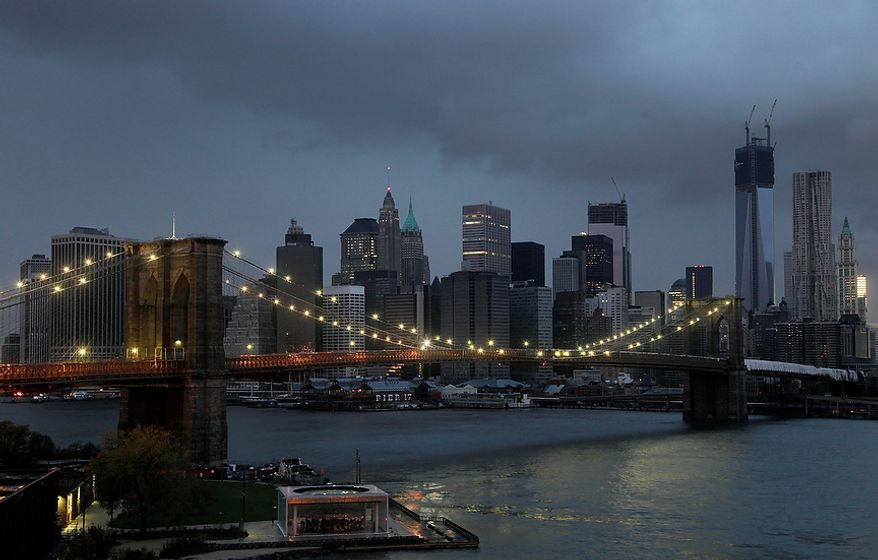The lights on the Brooklyn Bridge stand in contrast to the lower Manhattan skyline which has lost its electrical supply, Tuesday, Oct. 30, 2012, after megastorm Sandy swept through New York. A record storm surge that was higher than predicted along with high winds damaged the electrical system and plunged millions of people into darkness. (AP Photo/Mark Lennihan)