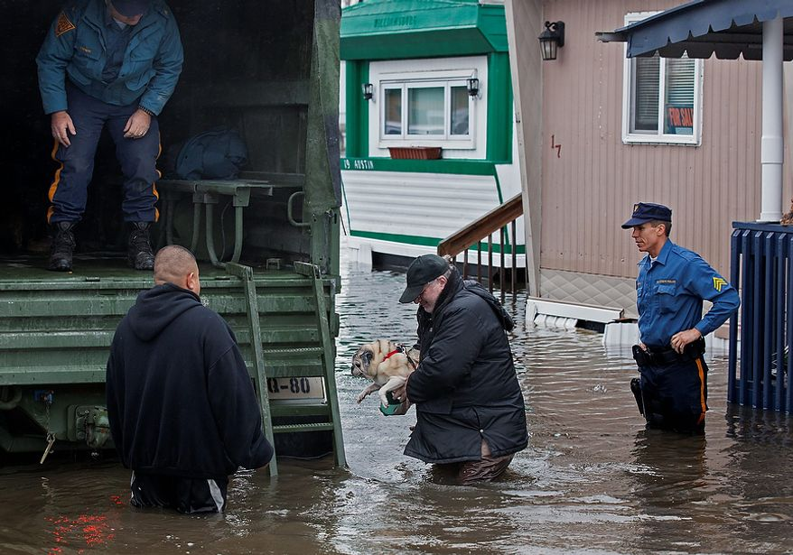 With the aid of New Jersey State police, a man walks with his dog to a National Guard vehicle after leaving his flooded home at the Metropolitan Trailer Park in Moonachie, N.J., Tuesday, Oct. 30, 2012, in the wake of superstorm Sandy. Sandy arrived along the East Coast and morphed into a huge and problematic system, putting more than 7.5 million homes and businesses in the dark and causing a number of deaths. (AP Photo/Craig Ruttle)
